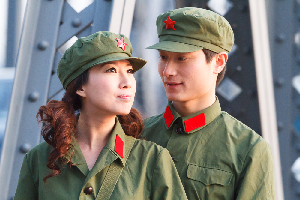 A young couple dressed in people's army uniform posing in Waibaidu bridge